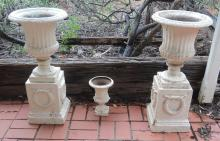 A PAIR OF WHITE PAINTED CAST IRON URNS ON PEDESTALS; TOGETHER WITH A SMALLER WHITE PAINTED CAST IRON URN