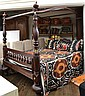 A MAHOGANY KING SIZED FOUR POSTER BED WITH CANOPY TOGETHER WITH A SUZANI BEDSPREAD AND SIX COORDINATING SUZANI CUSHIONS