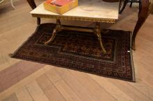 A MIDDLE EASTERN PRAYER RUG IN COPPER AND NAVY TONES