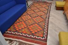 A FLAT WEAVE RUG WITH GEOMETRIC PATTERN IN ORANGE AND GREEN TONES