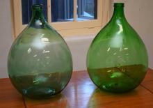 A PAIR OF GREEN GLASS DEMI JOHNS