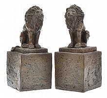 A PAIR OF COMPOSITE LIONS ON SOCLES