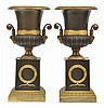 A PAIR OF BRONZE AND GILT BRONZE NEO CLASSICAL URNS ON SOCLES