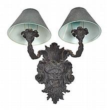 A ROCOCO STYLE BRONZE WALL SCONCE  the back plate cast with foliage and a mask head emanating two scroll arms, 37cm high