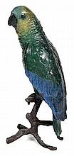 A COLD PAINTED BRONZE FIGURE OF A PARROT  with green, red and blue plumage, perched upon a realistically cast branch, 29.5cm high