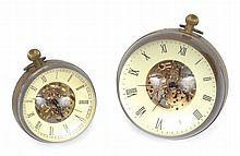 TWO BRASS AND GLASS SPHERICAL DESK CLOCKS WITH EXPOSED MOVEMENTS each with roman numerals on a white dial around exposed movements, the larger 8.5cm diameter and the smaller 6.5cm diameter