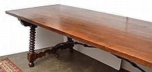 A SPANISH STYLE OAK REFECTORY TABLE  rectangular, with angled ring turned supports and a wrought iron stretcher, 300 x 80.5 x 100cm