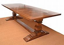 AN OAK REFECTORY TABLE the rectangular top with panelled inlay, above two turned supports united by a stretcher, 265 x 77 x 104cm