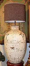 A PAIR OF CHINESE GLAZED EARTHENWARE STORAGE JARS CONVERTED TO LAMP BASES, WITH MODERN SHADES the jars glazed in white with calligraphy, (wear), the lamp bases 71cm high