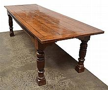 A CHARLES II STYLE REFECTORY TABLE  with a planked rectangular top above a frieze carved to one side with a scalloped border raised on turned legs, 268 x 80 x 92cm