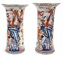 A PAIR OF JAPANESE IMARI VASES  each with a flared rim, the cylindrical body decorated with scenes of birds and plants in a mountain setting between bands of decoration, 45.5cm high