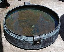 AN INDIAN BEATEN COPPER KENDI  shallow circular with scroll handles, 99cm wide across the handles