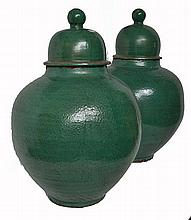 A PAIR OF OVOID MOROCCAN GLAZED EARTHENWARE JARS WITH DOMED LIDS  74cm high