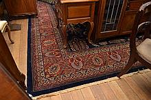 A LARGE QUALITY ORIENTAL PILE RUG IN NAVY AND RED PATTERNS (6M X 3M)