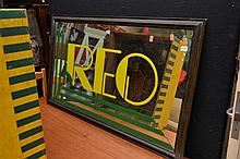 A FRAMED MIRROR WITH PAINTED 'REO' GRAPHIC
