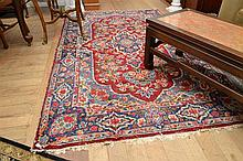 A LOVELY WORN WOOLEN RUG IN RED, BLUE AND CREAM TONES