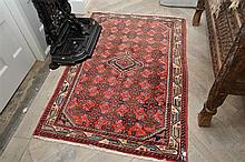 A SMALL AFGHAN TRIBAL RUG IN RED, GREEN AND BLUE TONES