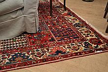 AN AFGHAN RUG IN RED, CREAM AND NAVY TONES (300cm X 215cm)