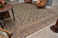 A LARGE PERSIAN RUG IN OLIVE AND CREAM TONES (400cm X 300cm).