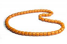 A STRING OF FIFTY BARREL SHAPED AMBER BEADS, 30cm long