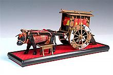 TWO JAPANESE MINIATURE FIGURES, black & gold lacquer, with brocade trimmings The oxcart 15cm high