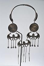 A MEO TRIBE COILED SILVER NECKBAND, bat decoration to front, alongside a set of opium implements