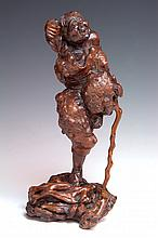 A CARVED ROOTWOOD FIGURE OF LOHAN, modelled with one leg raised, leaning on his staff, 27.5cm high