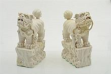 A PAIR OF BLANC DE CHINE FO DOGS, modelled as male with globe and female with cub 26.5cm high