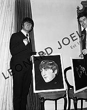 JOHN LENNON POSING WITH PORTRAIT OF HIMSELF