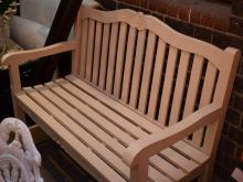 A WHITE PAINTED FRENCH PROVINCIAL STYLE OUTDOOR BENCH SEAT