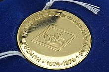 AN O&K ORENSTEIN AND KOPPEL GOLD MEDALLION IN 18CT GOLD