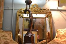 GILTWOOD FRAMED CUSHION FRONTED WALL MIRROR, WITH A CARVED CLASSICAL TROPHY AND FOLIATE CHEST