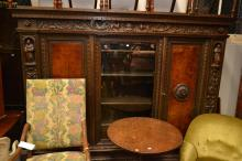 A HEAVILY CARVED AND ORNATE GOTHIC REVIVAL DISPLAY CABINET WITH BURR WALNUT PANELS AND FIGURAL CARVING