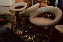 A SET OF FOUR ADJUSTABLE CHROME AND CREAM LEATHER BAR STOOLS