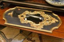 A SMALL BLACK AND GILT WALL MIRROR