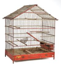 A RED PAINTED WOOD AND METAL BIRDCAGE, WITH A POINTILATED ROOF, 66 X 74 X 42CM