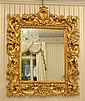 A LARGE BAROQUE STYLE GILT WALL MIRROR SURMOUNTED ON EACH SIDE WITH STANDING CHERUBS H180XW150 APPROX
