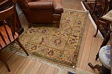 AN INDIAN ARMITSAL HALL RUG IN GOLD, GREEN AND BURGUNDY TONES