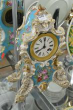 A 19TH CENTURY CONTINENTAL PORCELAIN CLOCK WITH HANDPAINTED FLORAL DETAIL