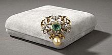 Broche en or jaune à décor d'entrelacs sertie de diamants, d'une émeraude