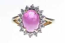 A ruby and diamond cluster ring The oval cabochon-cut ruby, to a round bril