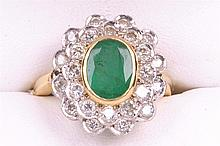 An emerald and diamond cocktail ring The central oval mixed cut emerald of