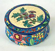 A Longwy French faience ware circular trinket pot and cover Painted in enam
