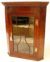 A Georgian inlaid mahogany hanging corner cupboard The moulded cornice abov