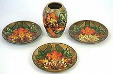 Four pieces of Moorcroft pottery decorated in the Flame of the Forest patte