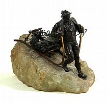 A bronze figure of a Alpine huntsman dragging a dead deer on a sledge late