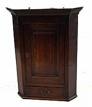 A George III oak hanging corner cupboard The moulded tapered cornice above