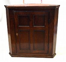 A George III oak hanging corner cupboard The moulded cornice above quarter