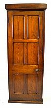 A late Victorian pitch pine tall cupboard The plain cornice above a panelle