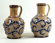 Royal Doulton Lambethware, pair of bulbous form jugs Each having relief scr